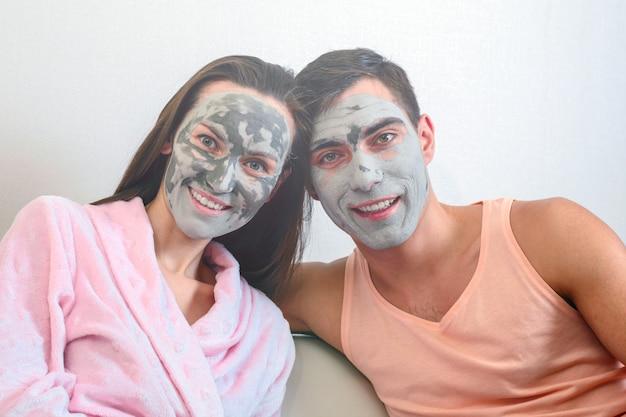 Emotioneel portret van een echtpaar in maskers gemaakt van klei. dag spa, wellness, huidverzorging