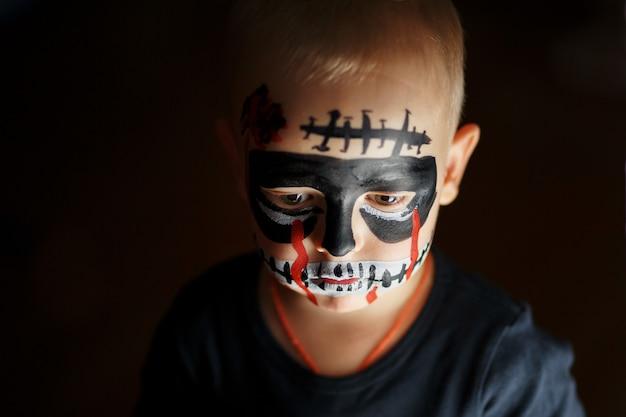 Emotioneel portret van een jongen met een enge zombie op zijn gezicht