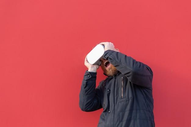 Emotioneel portret van een man op straat met een realiteitsbril tegen de achtergrond van een rode muur