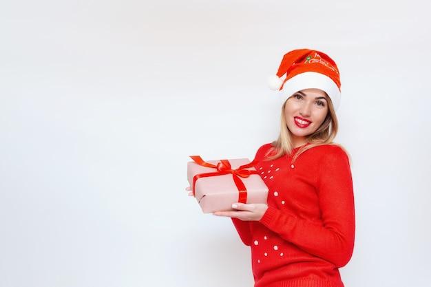 Emotioneel portret van een meisje in een kerstmuts met een cadeau in haar handen