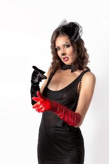 Emotioneel portret van een meisje in een zwarte jurk en zwarte en rode handschoenen