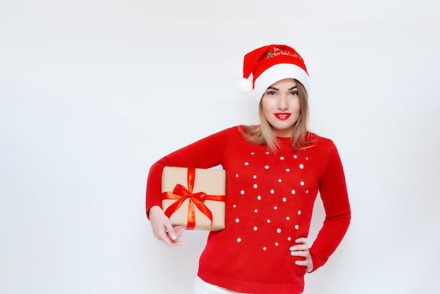Emotioneel portret van een meisje met een geschenkdoos in haar handen in een kerstmuts