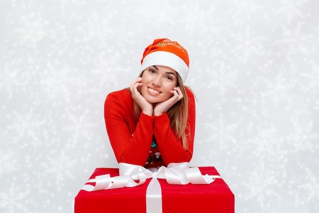 Emotioneel portret van een meisje met een kerstmuts en een rode geschenkdoos met een witte strik