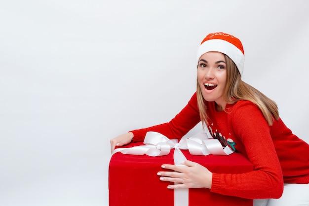 Emotioneel portret van een mooi meisje in een kerstmuts en een rode geschenkdoos