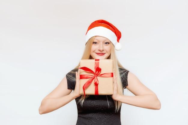 Emotioneel portret van een mooi meisje met een geschenkdoos in haar handen in een kerstmuts
