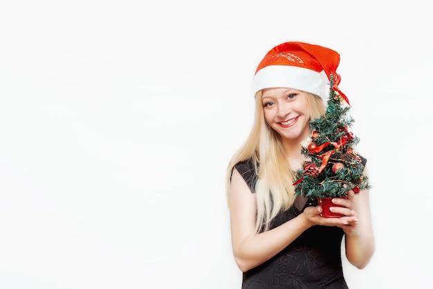 Emotioneel portret van een mooi meisje met een kerstmuts en een kerstboom in haar handen