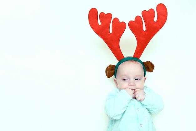 Emotioneel portret van een pasgeboren baby in kerstrendiergewei