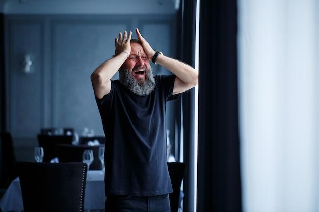 Emotioneel portret van een volwassen grijsharige man met een baard in een zwart t-shirt
