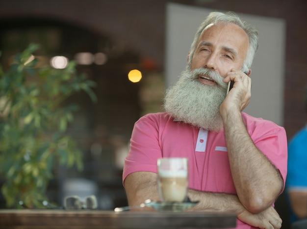 Emotioneel portret van een vrolijke en stijlvolle volwassen zakenman met een kaal hoofd, met een glimlach praten op de smartphone met een vriend. senior man met baard