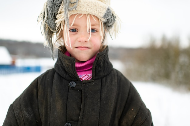 Emotioneel portret van positief slavisch meisje dat losse pasvorm gewatteerde jas met sjaal draagt