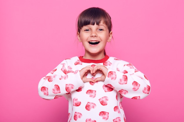 Emotioneel positief donkerharig meisje dat met opgewonden blik naar camera kijkt, hartvorm met vingers toont, liefde uitdrukt, witte sweater draagt, die over roze muur wordt geïsoleerd.