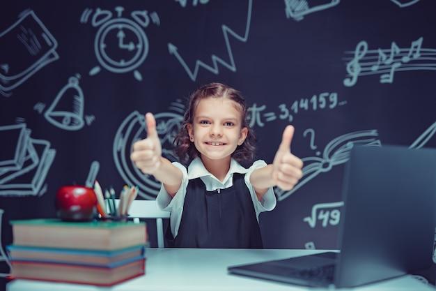Emotioneel schoolmeisje dat duimen laat zien en inspiratie of oplossing vindt die aan een bureau zit met een laptop en een...