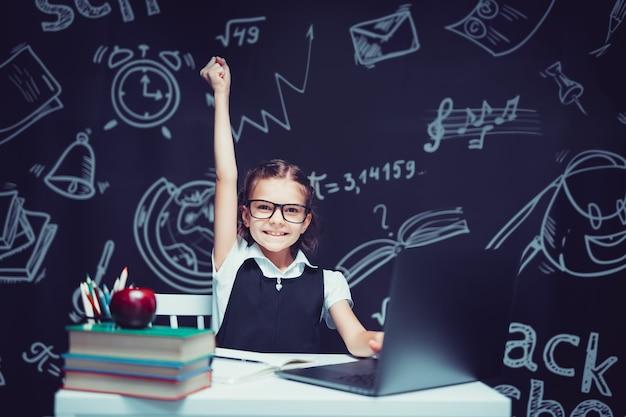 Emotioneel schoolmeisje wijzende vinger omhoog denkend en vindend inspiratie of oplossing zittend aan bureau...