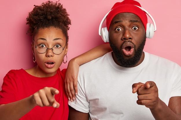 Emotioneel stomverbaasd etnische jonge vriend en vriendin wijzen naar de camera, merken iets ongelofelijks op, hebben angstige blikken, man draagt stereokoptelefoon op oren. omg-concept