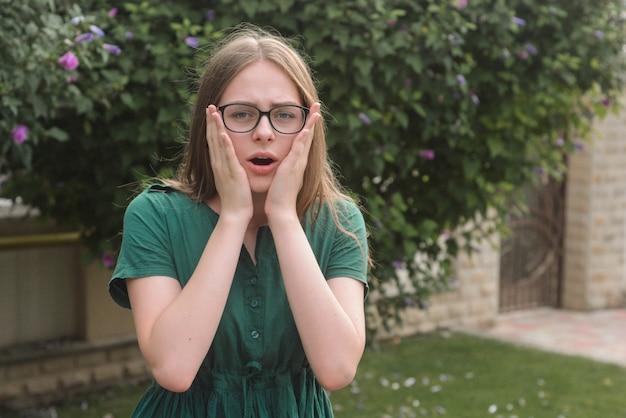 Emotioneel surpirized tiener leeftijd meisje, in groene jurk