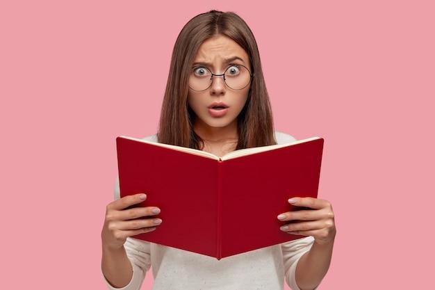 Emotioneel verrast europese vrouw houdt leerboek vast, heeft gezichtsuitdrukking bang, maakt zich zorgen voordat ze het toelatingsexamen haalt, draagt een ronde bril die over een roze muur wordt geïsoleerd. vrouwelijk meisje met rood boek