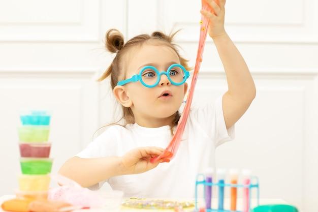 Emotioneel verrast kind dat slijm in grappige glazen maakt