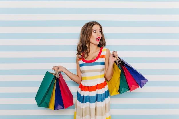 Emotioneel, verrast meisje in gestreepte veelkleurige jurk poseren met boodschappentassen. portret van brunette met rode lippenstift op gestreepte muur