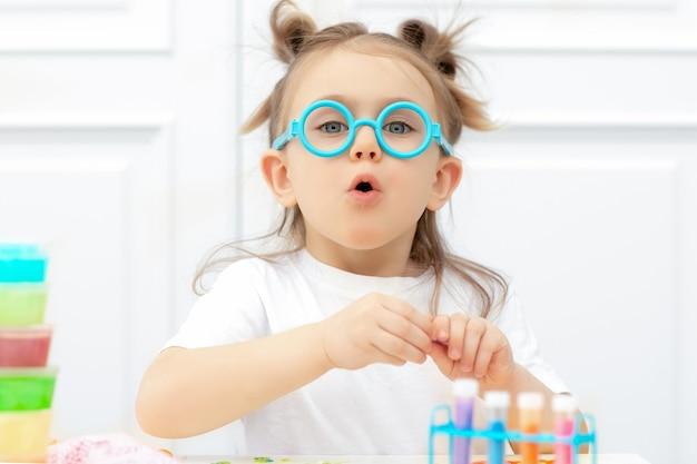 Emotioneel verrast schattig jong geitje in grappige glazen. kleine meisje wetenschapper plezier maken van experimenten in het laboratorium