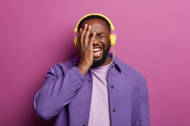 Emotioneel vreugdevol kan niet stoppen met lachen, houdt de handpalm op het gezicht, is dolgelukkig met gezichtsuitdrukking, luistert naar muziek via moderne stereohoofdtelefoons