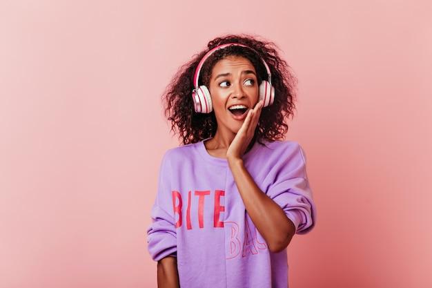 Emotioneel vrouwelijk model met zwart krullend haar dat van muziek geniet. gelukkig afrikaans meisje in hoofdtelefoons die verbazing uitdrukken.