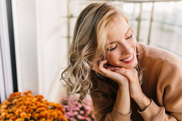 Emotioneel wit meisje dat met gesloten ogen glimlacht. portret van enthousiaste krullende vrouw zit in de buurt van oranje bloemen.