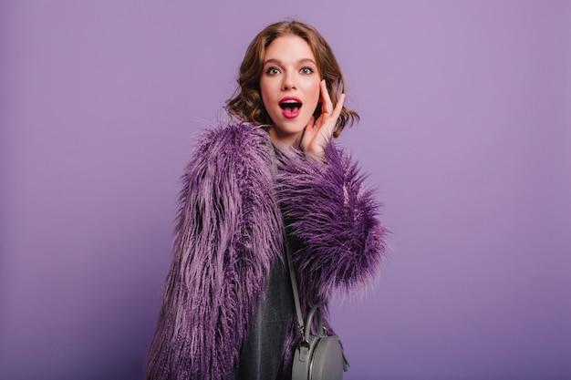Emotioneel wit meisje met kleurrijke make-up die zich voordeed op paarse achtergrond met tas