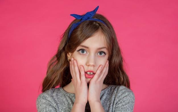 Emotionele 8-jarige schattige tienermeisje denken en kijken camera, geïsoleerd tegen roze achtergrond. kaukasisch kind in vrijetijdskleding toont verrassing en onverwachte gebeurtenis. ruimte voor site kopiëren