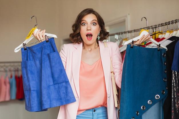 Emotionele aantrekkelijke vrouw met kleding op hanger in kledingwinkel