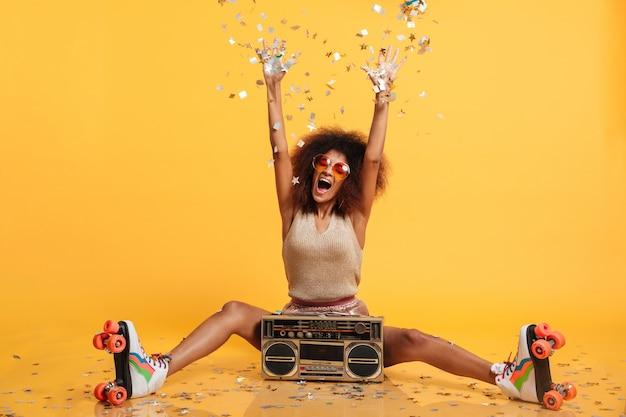 Emotionele afrikaanse disko vrouw in retro slijtage en rolschaatsen gooien confetti zittend met boombox