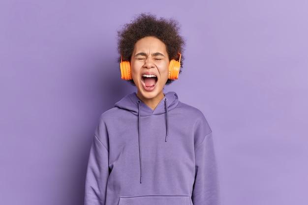 Emotionele afro-amerikaanse vrouw schreeuwt luid houdt mond geopend gekleed in hoodie.