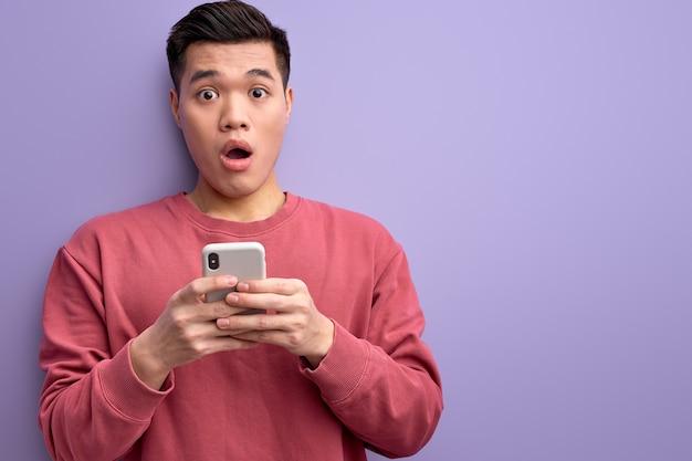 Emotionele aziatische man chatten met iemand op smartphone, geschokt door nieuws