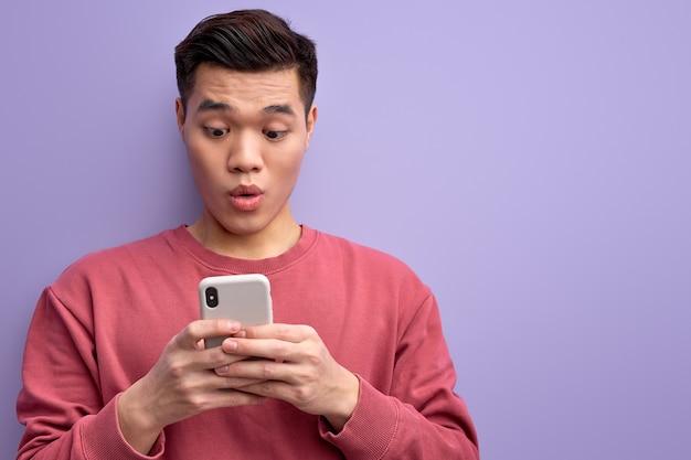 Emotionele aziatische man chatten met iemand op smartphone, staan in shock