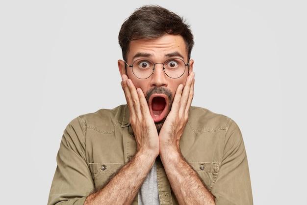 Emotionele bang geschokte man met wijd geopende mond hoort indrukwekkend gerucht, staart met een verbijsterde uitdrukking, stomverbaasd zijn, draagt een ronde bril, geïsoleerd over een witte muur