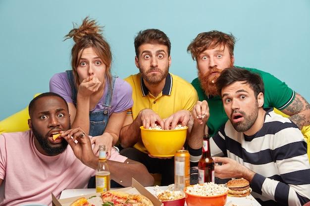 Emotionele bange duizendjarige vrienden brengen samen vrije tijd door, kijken online spannende films, eten lekkere pizza, drinken bier, hebben interesse in hun blik, geïsoleerd tegen een blauwe muur, genieten van televisie.