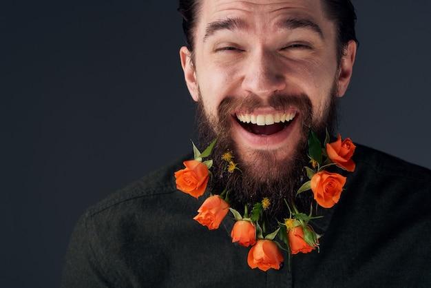 Emotionele bebaarde man bloemen romantiek close-up donkere achtergrond.