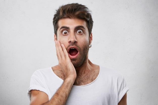 Emotionele bebaarde man die zijn hand op de wang houdt terwijl hij kijkt met ogen die eruit springen en opende mond wordt bang tijdens het kijken naar horrorfilm. jonge man met enge blik