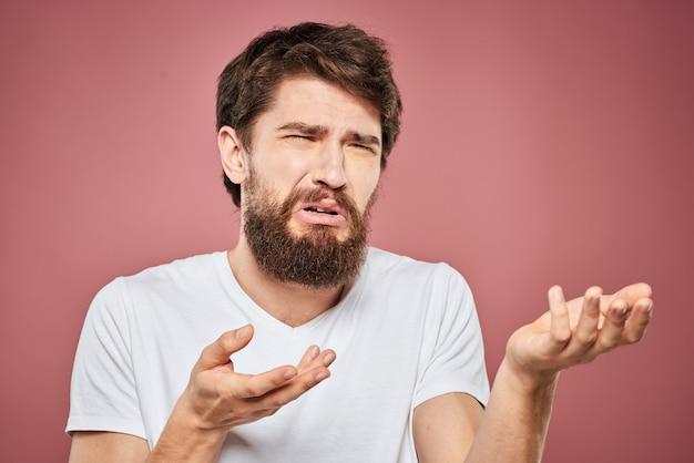 Emotionele bebaarde man in wit t-shirt ontevredenheid geïsoleerd