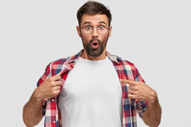 Emotionele bebaarde man met verbijsterde uitdrukking wijst naar zijn witte t-shirt, toont lege ruimte voor uw ontwerp, reageert op hoge prijs, geïsoleerd over witte muur. verontwaardigd jong mannetje