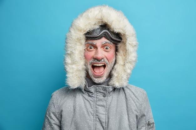 Emotionele bevroren man schreeuwt luid, heeft een rood gezicht bedekt met ijs, gekleed in een thermojack met capuchon en een snowboardbril.