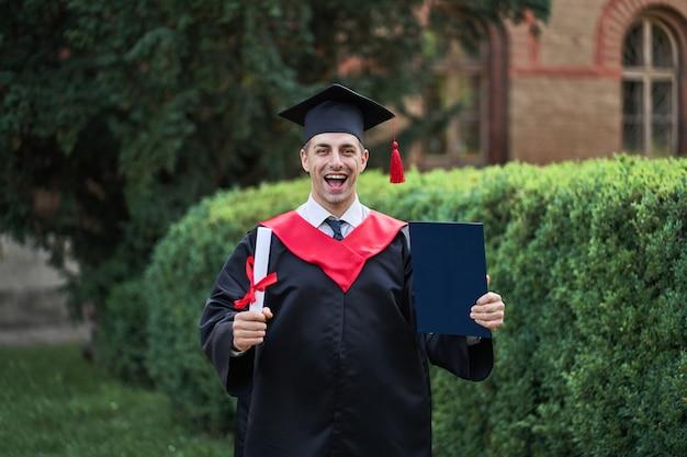 Emotionele blanke afgestudeerde in afstudeergewaad en diploma op de universiteitscampus.