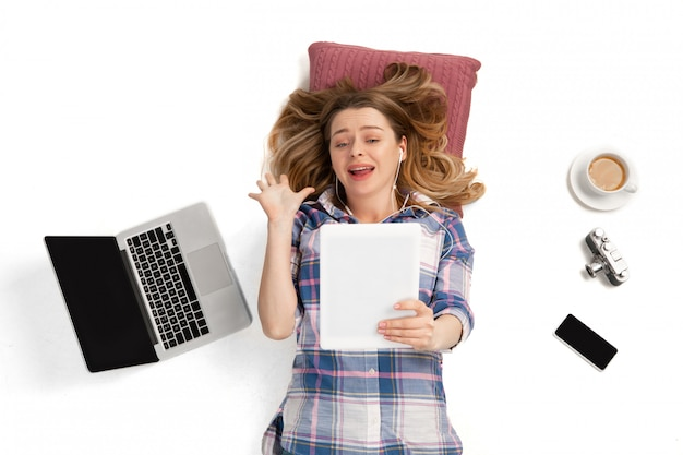 Emotionele blanke vrouw met behulp van gadgets, technologieën. apparaten die mensen verbinden tijdens quarantaine