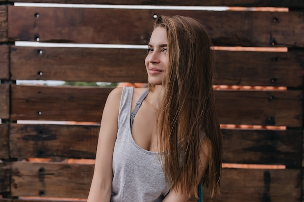Emotionele blanke vrouw met lang haar poseren in de warme ochtend van de lente. foto van prachtig kaukasisch meisje dat op houten muur wordt geïsoleerd.
