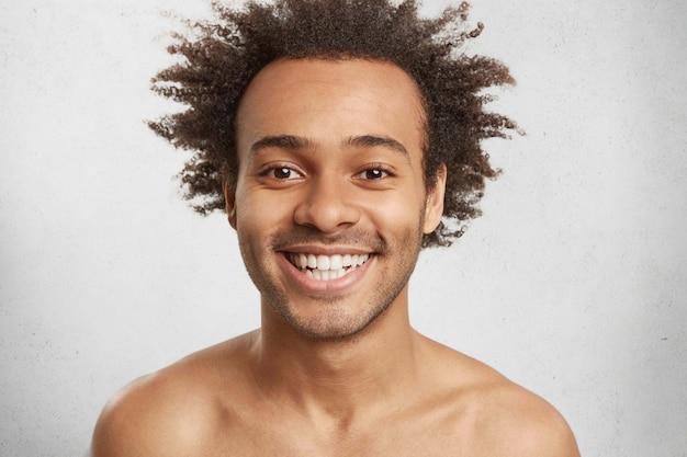 Emotionele blije glimlachende man heeft een aantrekkelijk uiterlijk, borstelige afro-haarstijl, witte, gelijkmatige tanden