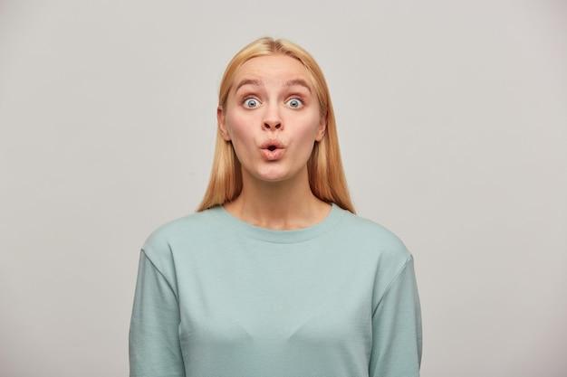 Emotionele blonde jonge vrouw, die erg verrast kijkt, met open ogen, fluit van verbazing