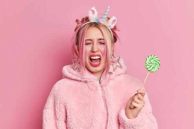 Emotionele blonde jonge vrouw roept luid houdt ogen gesloten draagt professionele lichte make-up heeft plezier houdt lolly draagt warme jas
