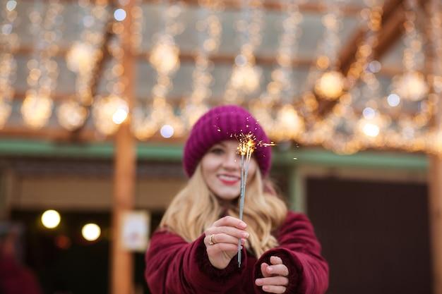 Emotionele blonde vrouw gekleed in warme kleren, met gloeiende sterretjes op de kerstmarkt