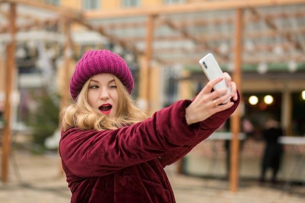 Emotionele blonde vrouw gekleed in warme kleren selfie maken op de achtergrond van garland in kiev