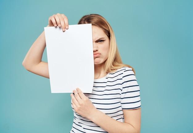 Emotionele blonde vrouw met een wit vel papier in haar handen op een blauwe muur.
