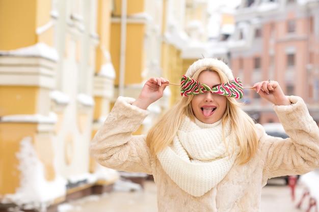 Emotionele blonde vrouw met lang haar met een warme gebreide muts, met heerlijke kerstsnoepjes in de buurt van haar gezicht